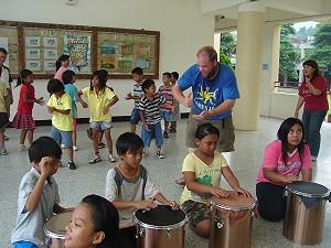 外籍森巴鼓的教學老師(穿藍衣),在教學中也手足舞蹈,敲鼓場外的老師與小朋友情不自禁的也隨鼓樂翩翩起舞,場面充滿樂性動感 之樂。《攝影/賴約翰》