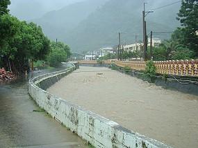 餉潭大橋赤褐色的水已漫滿整個河道,遠處山與本河流交匯處為排灣族的來義鄉。《攝影/賴約翰》